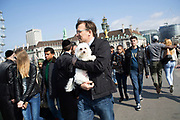 Man carrying his pet dog across Westminster Bridge amid tourists in London, UK.