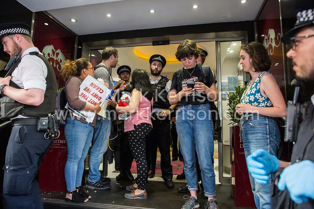 London, UK. 1 June, 2019. Police officers attempt to move members of United Voices of the World (UVW), a grassroots trade union representing mainly migrant workers, supported by the Independent Workers of Great Britain (IWGB) trade union, protesting outside the DoubleTree Hilton Hotel in solidarity with Dalia Quinonez Guerrero (l), a former cleaner at the hotel from whom wages were withheld. The protest was originally arranged to take place outside Chanel but was moved after the global luxury fashion chain agreed to pay its cleaners the London Living Wage.