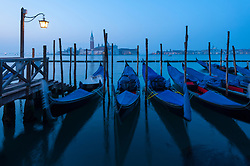 Dawn view of gondolas moored in Venice , Italy