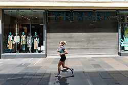 Glasgow, Scotland, UK. 12 June 2020.  Although shops can reopen in England next week, in Scotland the lockdown is not being relaxed so quickly with several more weeks of restrictions to go. Shops and businesses remain closed and streets are very quiet. Pictured; jogger runs past Primark store on Argyle Street which is still closed.  Iain Masterton/Alamy Live News
