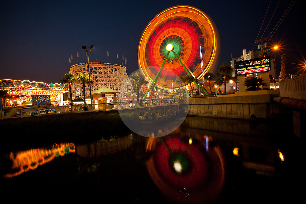 The Ferris Wheel and roller coaster reflected in the ocean at Family Kingdom amusement park along the beachfront in Myrtle Beach, SC.