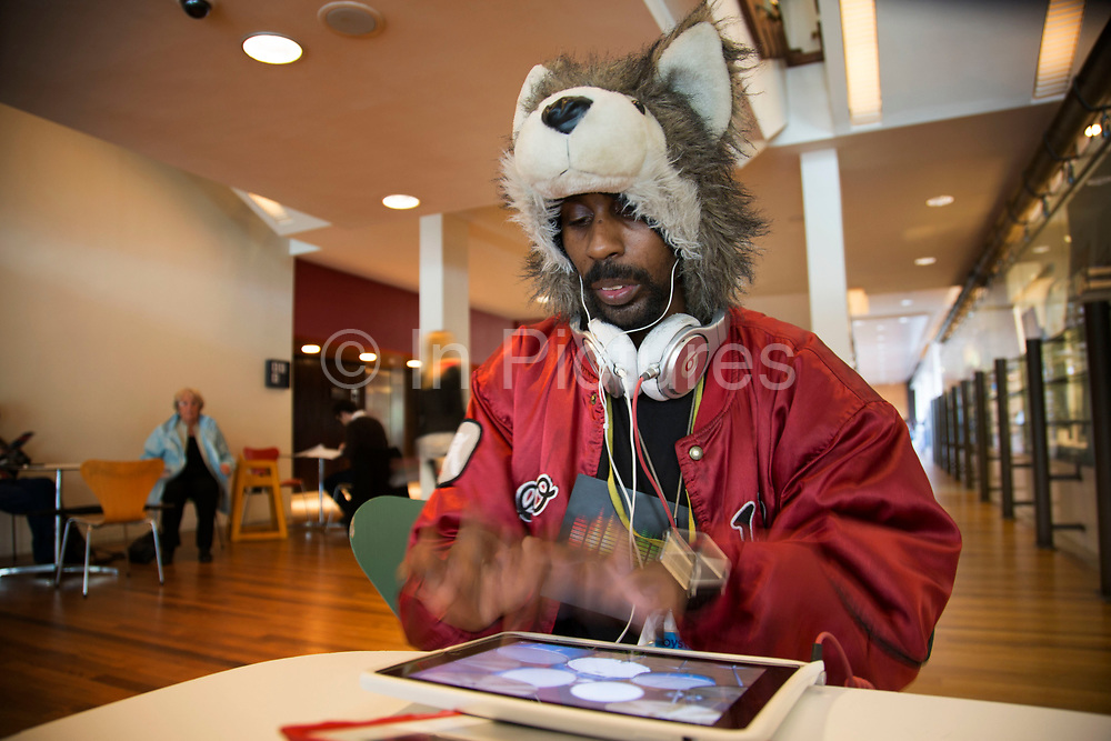 Man wearing an animal hat playing drum machine at the Royal Festival Hall. This character is a regular around the Southbank Centre, playing drums on his iPad whilst listening to music on his headphones. The South Bank is a significant arts and entertainment district, and home to an endless list of activities for Londoners, visitors and tourists alike.