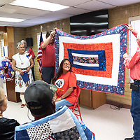 Melanie Metzler, center, smiles as she is presented her quilt from John Matajcich, left, and Mayor Jackie Mckinney, right at the Veterans Helping Veterans building in Gallup Friday.