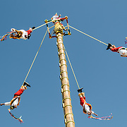 Swinging from a tall pole suspended only by ropes, performers recreating a traditional Mayan ceremony at Xcarat Maya theme park south of Cancun and Playa del Carmen on Mexico's Yucatana Peninsula.