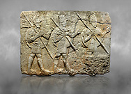 Hittite monumental relief sculpted orthostat stone panel from the Herald's Wall. Basalt, Karkamıs, (Kargamıs), Carchemish (Karkemish), 900-700 B.C. Military parade. Anatolian Civilisations Museum, Ankara, Turkey. Two helmeted soldiers in short skirts carry the shield on their backs and the spears in their hands.  <br /> <br /> Against a grey art background. .<br />  <br /> If you prefer to buy from our ALAMY STOCK LIBRARY page at https://www.alamy.com/portfolio/paul-williams-funkystock/hittite-art-antiquities.html  - Type  Karkamıs in LOWER SEARCH WITHIN GALLERY box. Refine search by adding background colour, place, museum etc.<br /> <br /> Visit our HITTITE PHOTO COLLECTIONS for more photos to download or buy as wall art prints https://funkystock.photoshelter.com/gallery-collection/The-Hittites-Art-Artefacts-Antiquities-Historic-Sites-Pictures-Images-of/C0000NUBSMhSc3Oo