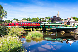 © Licensed to London News Pictures. 18/07/2018. Ruswarp UK. Vintage 1965 Diesel locomotive D7629 travels on the North Yorkshire Moors Railway across the river Esk in the picturesque village of Ruswarp, north Yorkshire this morning. Photo credit: Andrew McCaren/LNP