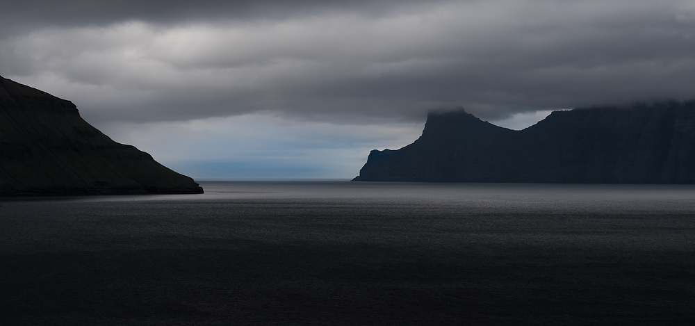 Landscape shot of fjord with silhouettes of cliffs against the horizon