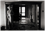 A cowboy stands in the archway of a room inside of his western home