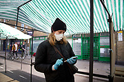 Daily life continues but not as as normal with some rules and restrictions in Hackney on 21st March 2020 in London, United Kingdom. Broadway market on a Saturday morning. Stall holder wearing a face mask and gloves amidst empty stalls.