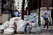 Rubbish bags piled high awaiting collection in central London. This unsightly load of trash mainly from local businesses makes for an ugly sight in an area of London very populated by tourists.