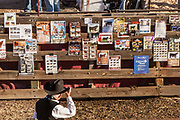 Cattleman looks at cattle posters on the fence at the Denver Stock.