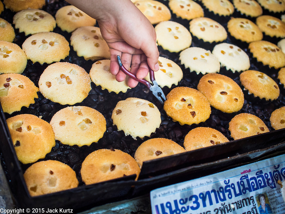 """06 FEBRUARY 2015 - BANGKOK, THAILAND: A worker at Thanusingha Bakery pulls traditional Thai Catholic desert cakes out of the baking pans. The cakes are called """"Kanom Farang Kudeejeen"""" or """"Chinese Monk Candy."""" The tradition of baking the cakes, about the size of a cupcake or muffin, started in Siam (now Thailand) in the 17th century AD when Portuguese Catholic priests accompanied Portuguese soldiers who assisted the Siamese in their wars with Burma. Several hundred Siamese (Thai) Buddhists converted to Catholicism and started baking the cakes. When the Siamese Empire in Ayutthaya was sacked by the Burmese the Portuguese and Thai Catholics fled to Thonburi, in what is now Bangkok. The Portuguese established a Catholic church near the new Siamese capital. Now just three families bake the cakes, using a recipe that is 400 years old and contains eggs, wheat flour, sugar, water and raisins. The same family has been baking the cakes at the Thanusingha Bakery, near Santa Cruz Church, for more than five generations. There are still a large number of Thai Catholics living in the neighborhood around the church.        PHOTO BY JACK KURTZ"""