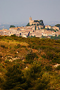 The village with the church in the middle. St Pargoire. Languedoc. Garrigue undergrowth vegetation with bushes and herbs. France. Europe.