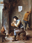 Smoker in front of a fireplace. Painting by David Teniers the Younger (1610-1690) Flemish artist. Man seated on upturned barrel in front of a fire is lighting a clay pipe. Peasant Domestic Interior Jug Ceramic Tobacco