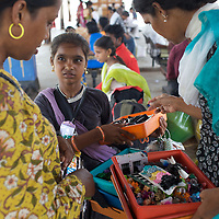 Kalki Subramaniam, an activist for the rights of transgenders, (left) shops for hair bands with a transgender friend on a trains station platform in Chennai. ..India's transexual community has a recorded history of more than four thousand years. Many consider the The Third Sex, also known as Aravanis, to posses special powers allowing them to determine the fate of others. As such, they are not only revered but despised and feared too. Resigned to the fringes of society, segregated and excluded from most occupations, many Aravanis are forced to turn to begging and sex work in order to earn a living. ..The annual transgender festival in the village of Koovagam, near Vilappuram, offers an escape from this often desolate existence. For some, the week-long partying and frenetic sex trade that culminates in the Koovagam festival is about fulfilling lustful desires. For others, the gathering provides a chance for transgenders to bond, share experiences, join the wider homosexual gay-community and coordinate their campaign for recognition and tackle the challenge of HIV/AIDS. ..It is the Indian state of Tamil Nadu that the eighty-thousand-strong Aravani community has made advances in their fight for rights. In 2009, the Tamil Nadu state government began providing sex-change surgery free of cost. The state has also offers special third-gender ration cards, passports and reserved seats in colleges. And 2008 the launch of Ippudikku Rose, a Tamil talk-show fronted by India's first transgender TV-host and the release of a mainstream Tamil film staring an Aravani in the lead-role. ..These advances clearly signal a victory for south India's transgenders, but they have also exposed deep divisions within the community. There is a very real gulf that separates the majority poor from their potentially influential but often reticent, upper-class sisters. ..Photo: Tom Pietrasik.Chennai, Tamil Nadu. India.May 2009