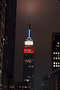 Empire State building with the national colors glowing at night.