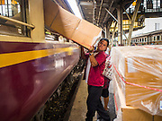 19 MARCH 2015 - BANGKOK, THAILAND:   A man offloads boxes through the window of a third class train from Ayutthaya after the train arrived at Hua Lamphong station in Bangkok. The State Railways of Thailand (SRT), established in 1890, operates 4,043 kilometers of meter gauge track that reaches most parts of Thailand. Much of the track and many of the trains are poorly maintained and trains frequently run late. Accidents and mishaps are also commonplace. Successive governments, including the current military government, have promised to upgrade rail services. The military government has signed contracts with China to upgrade rail lines and bring high speed rail to Thailand. Japan has also expressed an interest in working on the Thai train system. Third class train travel is very inexpensive. Many lines are free for Thai citizens and even lines that aren't free are only a few Baht. Many third class tickets are under the equivalent of a dollar. Third class cars are not air-conditioned.      PHOTO BY JACK KURTZ