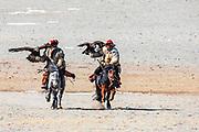 Kazakh eagle hunters riding in the Altai mountains with their golden eagles on horseback, Altai Mountains, Bayan Ulgii, Mongolia