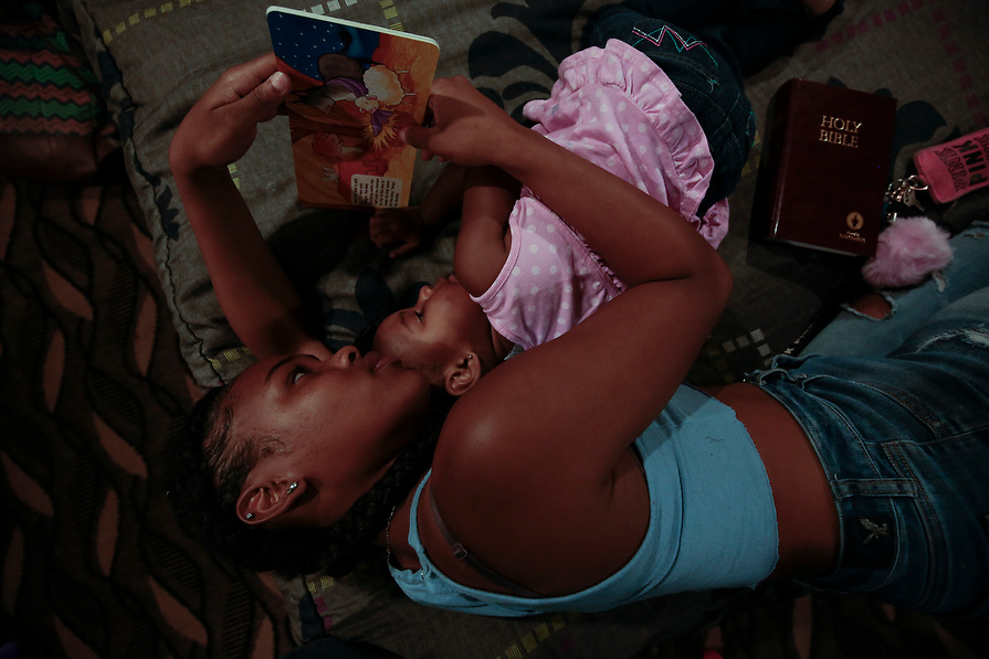 Joderrica Cornealius, 18, reads to her cousin, Elizabeth Thomas, 2, in a FEMA provided hotel room in the aftermath of tropical storm Harvey in Houston, Texas, U.S. September 10, 2017. Cornealius' home didn't flood, but she came to the hotel to show support to her family members who lost everything in the flood.