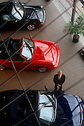An aerial view of a west London Porsche car salesman in his salesroom. We look down from a high vantage point to see three of his sports cars looking highly-polished in this expensive and exclusive market for elite cars. Two 911 (964) Carrera models from their 1992 range are seen in red and black - one an open top and the other a saloon. The Porsche 964 is the company's internal name for the version of the Porsche 911 model manufactured and sold between 1989 and 1994, designed by Benjamin Dimson in 1986 and built in Stuttgart, Baden-Württemberg, Germany.