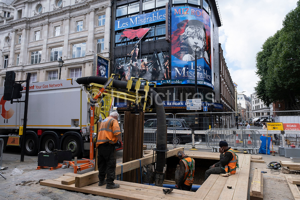 Gas technicians work in a deep hole in the ground underneath the poster for Les Miserables at the Sondheim Theatre on Shaftesbury Avenue, at the heart of Londons Theatreland on 10th August 2021 in London, United Kingdom. Theatreland has taken a big hit during the coronavirus pandemic as social distancing has not allowed audiences to return and so theatres were shut down. However now that audiences are allowed back the West End is coming to life once again.