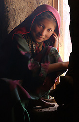 ANBAR SOMUCH, AFGHANISTAN, AUGUST 1, 2002:   Qubra sits in a window in the home which she and her family fled last year after Taliban forces raided the village of Anbar Somuch, Afghanistan, August 1, 2002. More than 100 families have returned to their village after the fall of the Taliban and they are rushing to rebuild their homes before the brutal winter sets in. (Photo by Ami Vitale)