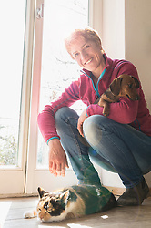 Mature woman with her pets at home, Bavaria, Germany