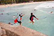 Two young boys with boogie boards jumps off a pier into the ocean in Waikiki.