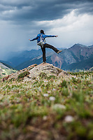 Female hiker watches approaching thunderstorms from Ice Lakes Basin, San Juan mountains, Colorado, USA