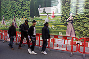 With a background of hanging hoarding media, young black men walk past a Dior shop being refurbished in central London.