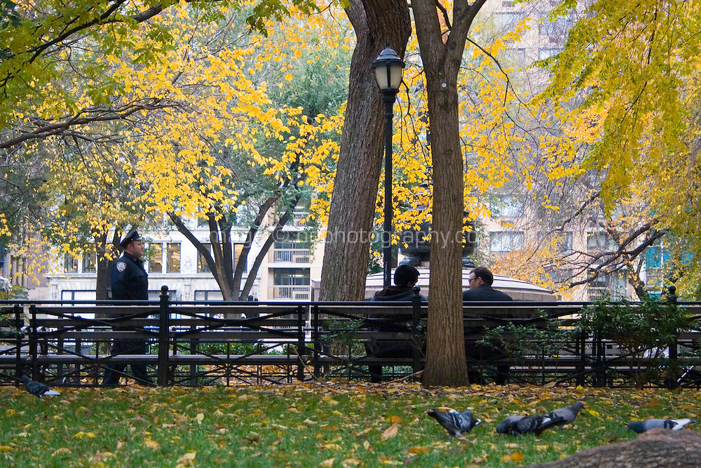 Two people chatting on a bench and a police man walking by at Union Square Park Manhattan New York