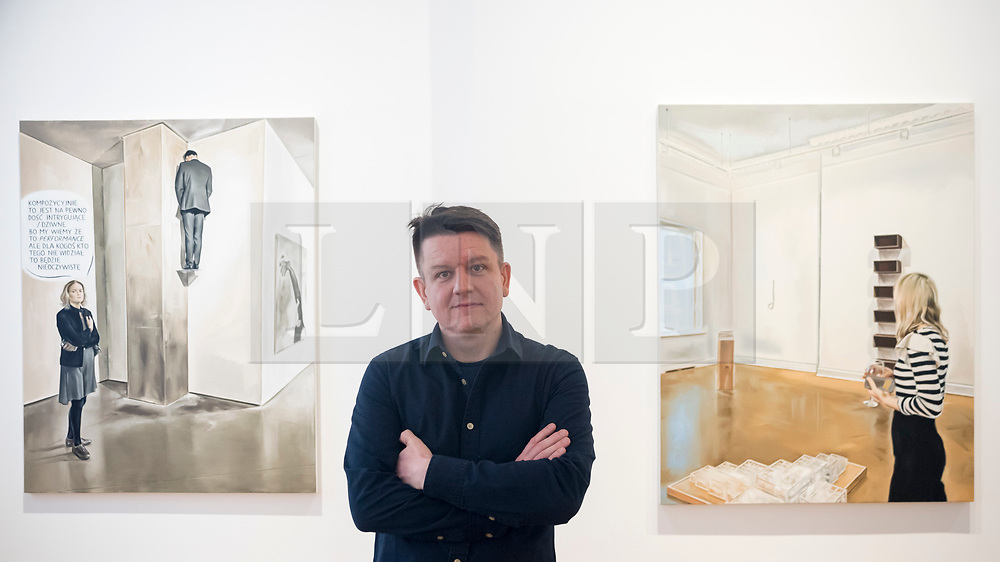 """© Licensed to London News Pictures. 28/11/2019. LONDON, UK. Polish artist Marcin Maciejowski poses with his works (L) """"It Certainly Has A Fairly Intriguing - Strange Composition"""" and (R) """"It Is Enough I'm Delighted, Don't Make Me Understand It"""", both 2019.  First look of """"Private View"""" by Marcin Maciejowski at Galerie Thaddeus Ropac in Mayfair.  The artist's first London exhibition features new large-scale paintings and graphic works on paper merging comic-book and Old Master traditions.  The show runs 28 November to 25 January 2020. Photo credit: Stephen Chung/LNP"""