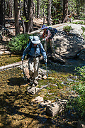 Hikers cross stepping stones over West Fork Green Creek at the outlet to Green Lake in Hoover Wilderness of Humboldt-Toiyabe National Forest, Eastern Sierra Nevada, Mono County, California, USA. Our backpack from Green Creek Trailhead to Summit Lake was 7.6 mi with 2360 ft gain, 310 ft descent, over a leisurely 3 days, then out on the fourth day. A day hike from our Green Lake campsite to West Lake was 3.9 mi with 1830 ft gain to 8896 ft elev. From Summit Lake, we day hiked east to Burro Pass with a view to Virginia Lakes (2180 ft gain over 4 miles round trip).