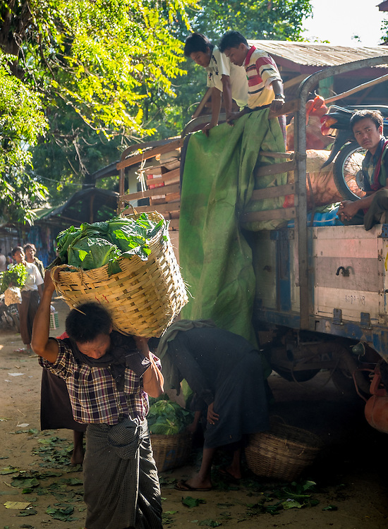 BAGAN, MYANMAR - CIRCA DECEMBER 2013: Man carrying vegetables in the Nyaung U market close to Bagan in Myanmar