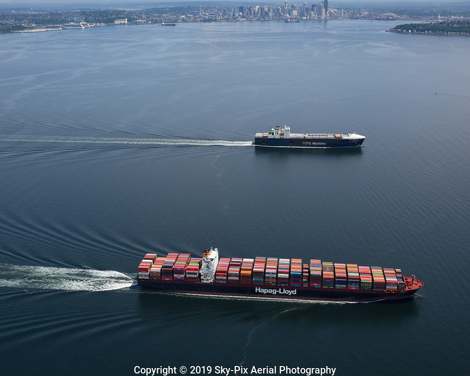 Two cargo ships underway in Puget Sound enroute to the Port Of Tacoma, passing by Elliott Bay and Seattle.