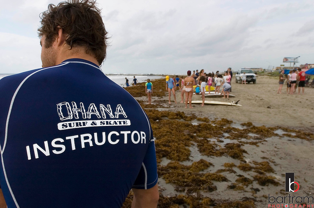 KEVIN BARTRAM/The Daily News.Ohana Surf Camp instructor Benjamin Walcher watches as campers gather on the beach near 28th Street and Seawall Boulevard on Tuesday, July 19, 2005. More than 80 kids participated in the third session of the camp.