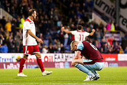 Ben Mee of Burnley cuts a dejected figure as Olympiakos celebrate victory - Mandatory by-line: Robbie Stephenson/JMP - 30/08/2018 - FOOTBALL - Turf Moor - Burnley, England - Burnley v Olympiakos - UEFA Europa League Play-offs second leg