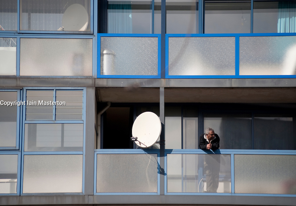Man on balcony of low cost apartment building in The Hague The Netherlands