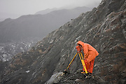 Dr. Tad Pfeffer, a glaciologist at the University of Colorado, installs a time lapse camera during a storm at the Columbia Glacier, near Valdez, Alaska.