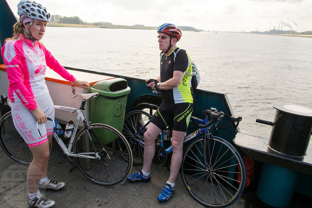 Twee wielrenners staan op de veerpont tussen Maassluis en Rozenburg.<br /> <br /> Two cyclist at a ferry between Maassluis and Rozenburg.