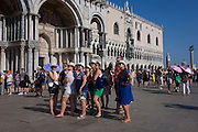 Tourists listen to tour guide in Piazza San Marco, Venice, Italy.
