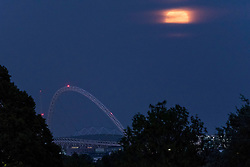 "© Licensed to London News Pictures. 07/05/2020. LONDON, UK.  A full moon, known this month as a Flower moon (named for the arrival of flowers in bloom in May), rises behind the arch of Wembley Stadium in north west London.  It is also the last ""supermoon"" to be seen in 2020, where the moon is closest to the earth (the perigee) and appears 6% larger than a normal full moon.  Wembley Stadium is under consideration to be a neutral venue to host Premier League games as part of Project Restart in order for the football season to reach a conclusion after being suspended due to the ongoing coronavirus pandemic.  Photo credit: Stephen Chung/LNP"