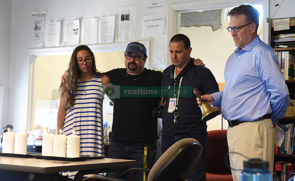 July 5, 2018 - Annapolis, Maryland, U.S. - RICK HUTZELL, right, the editor for the Capital Gazette, is joined by staff members, from left, reporter SELENE SAN FELICE, and photojournalists PAUL W. GILLESPIE and JOSHUA MCKERROW, as he rings a bell during a moment of silence at 2:33 p.m. to commemorate their fallen co-workers on Thursday. (Credit Image: © Brian Krista/TNS via ZUMA Wire)