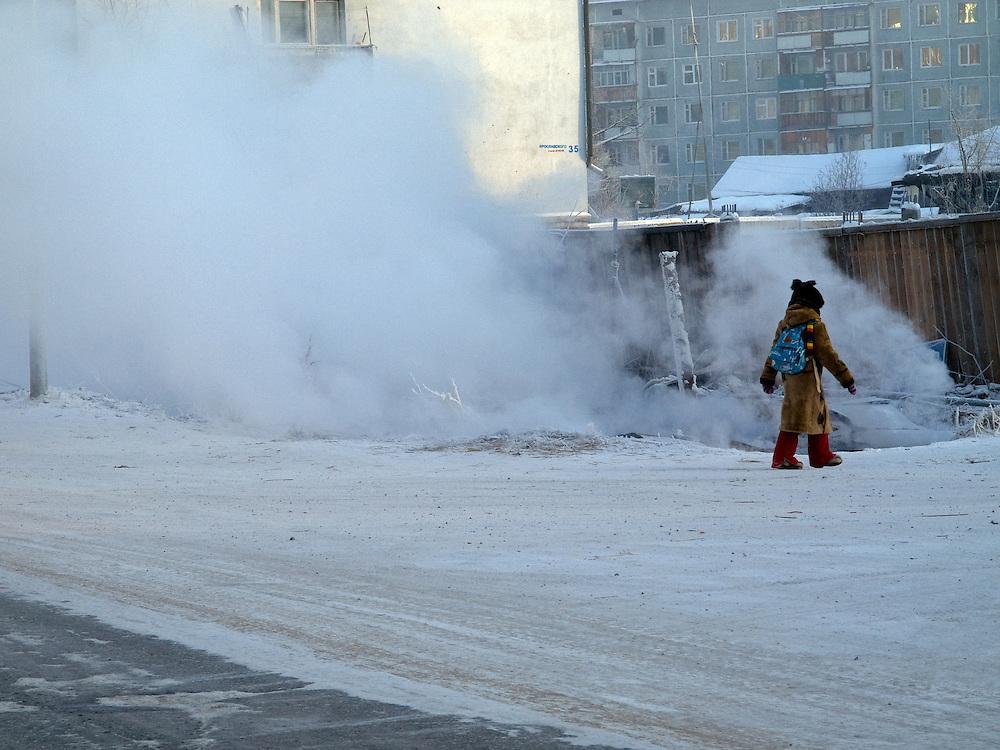 Schulmaedchen vor entweichendem Wasserdampf aus einer defekten Wasserleitung in Jakutsk. Jakutsk wurde 1632 gegruendet und feierte 2007 sein 375 jaehriges Bestehen. Jakutsk ist im Winter eine der kaeltesten Grossstaedte weltweit mit durchschnittlichen Winter Temperaturen von -40.9 Grad Celsius. Die Stadt ist nicht weit entfernt von Oimjakon, dem Kaeltepol der bewohnten Gebiete der Erde.<br /> <br /> Schoolgirl on a street in Yakutsk. Through a broken warm water pipe condensed water is very fast going up into the air. Yakutsk is a city in the Russian Far East, located about 4 degrees (450 km) below the Arctic Circle. It is the capital of the Sakha (Yakutia) Republic (formerly the Yakut Autonomous Soviet Socialist Republic), Russia and a major port on the Lena River. Yakutsk is one of the coldest cities on earth, with winter temperatures averaging -40.9 degrees Celsius.