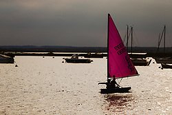 A sailing dinghy's magenta sail creates a splash of colour against the full sky at West Mersea, Mersea Island, near Colchester in Essex. West Mersea, Essex, July 11 2019.