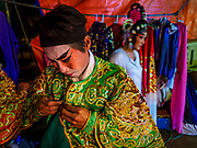 """26 FEBRUARY 2018 - BANGKOK, THAILAND: A performer gets into costume before a Chinese Opera at the Phek Leng Shrine in the Khlong Toey section of Bangkok. The shrine traditionally hosts a Chinese Opera just after the end of Lunar New Year festivities. Thailand is home to the largest population of overseas Chinese in the world, and Chinese cultural practices, like Chinese opera, called """"ngiew"""" in Thailand, are popular. Many of the performers are ethnic Thais who don't speak Chinese. They learn their lines phonetically.    PHOTO BY JACK KURTZ"""