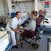 Nederland Rotterdam  31-08-2009 20090831 Foto: David Rozing .Serie over zorgsector, Ikazia Ziekenhuis Rotterdam. Afdeling neurologie, stroke unit, revalidatie  bejaarde man op zaal. Broeder praat met patient,   na de  oefeningen om opnieuw te leren lopen. De patient heeft een beroerte gehad en daardoor is oa zijn ( grove ) motoriek aangetast, deels verlamd geraakt. rolstoel, wheelchair.  Revalidation old patient, nurse talks to patient who has suffered a stroke. .Na een ernstige beroerte wordt u opgenomen in een gespecialiseerde afdeling of een afdeling intensieve zorgen van het ziekenhuis. Na de eerste 24 uur is het nodig om een aangepast revalidatieprogramma te starten. dat kan bestaan in wisselhoudingen en passieve bewegingen van de verlamde lichaamshelft.  .  ...Foto: David Rozing ..Holland, The Netherlands, dutch, Pays Bas, Europe, ronde doen, routine verpleegkundigen interactie patient verpleging, praatje maken met, tijd hebben voor, aandacht hebben voor geven,  hulp, helpen, verpleger, verplegers, verplegend, status., nursing, aansterken, handeling, handelingen,Holland, The Netherlands, dutch, Pays Bas, Europe, menselijk contact ,   oud, oude, op leeftijd, revalidatie, revalideren, revalidation, nursing,steun, steunen, warmte geven, helpen, hart onder de riem steken,aanmoedigen, moral support, blijk van affectie, steuntje in de rug,  steunbetuiging , mobiliteit, niet mobiel zijn, verlamd zijn, niet goed kunnen lopen, ondersteunen,zorgverlener, zorgverleners,zorgverlening,ondersteunen, helpen te met,moral support, blijk van affectie, steuntje in de rug,  steunbetuiging, verpleger, verplegers, verplegend