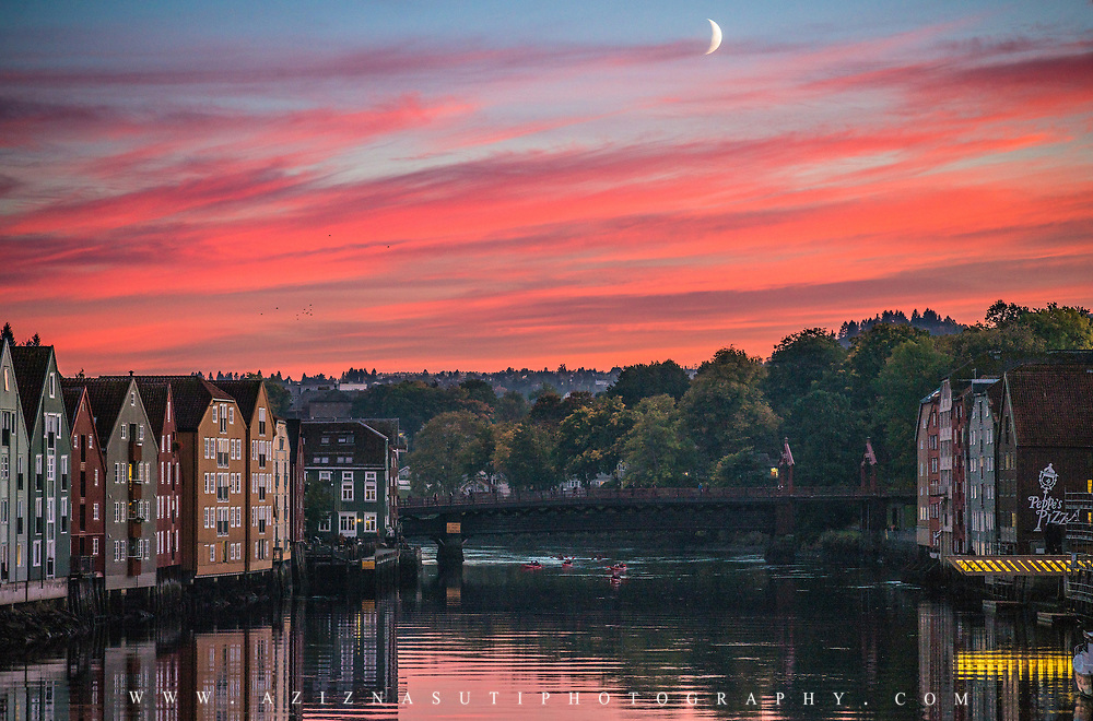 What do you need for a good landscape photo. Subject, colors, background, foreground and middle ground? Well here I have them all :). This is Trondheim where I have most of my photos from.  This picture has been taken with almost 50-60 years old Leica lens. I was lucky enough to spot the moon, kayak and birds to complement the photo. more photos:  Website  ,