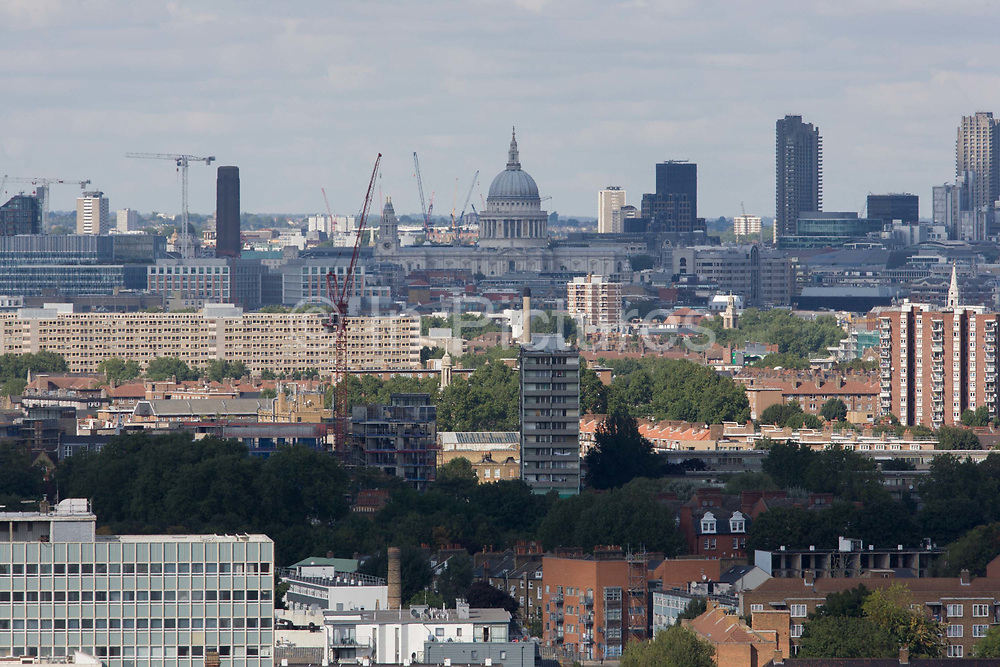 Aerial view of south London borough of Lambeth looking from Camberwell towards St Paul's Cathedral and Westminster. Tall tower blocks and wide estates occupy the skyline of this modern metropolis amid older Victorian and post-war homes. St Paul's itself rises most prominantly in the distance, its self-supporting dome designed by Sir Christopher Wren is one of the capital's most recognisable sights of London, with its dome, framed by the spires of Wren's City churches, dominating the skyline for 300 years. At 365 feet (111 m) high, it was the tallest building in London from 1710 to 1962, and its dome is also among the highest in the world. In terms of area, St Paul's is the second largest church building in the United Kingdom after Liverpool Cathedral.