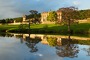 Chatsworth House reflecting in a mirror-like River Derwent. Derbyshire, Peak District, England, UK.